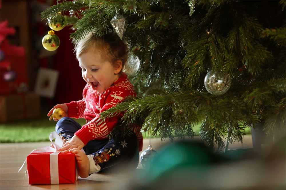 Baby sitting closely to an artificial Christmas tree